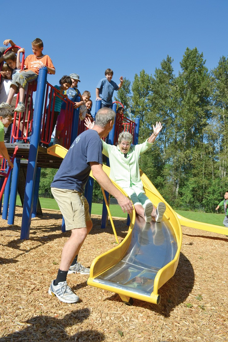 School board chair Laurae McNally tries out the curly slide on East Kensington Elementary's new playground