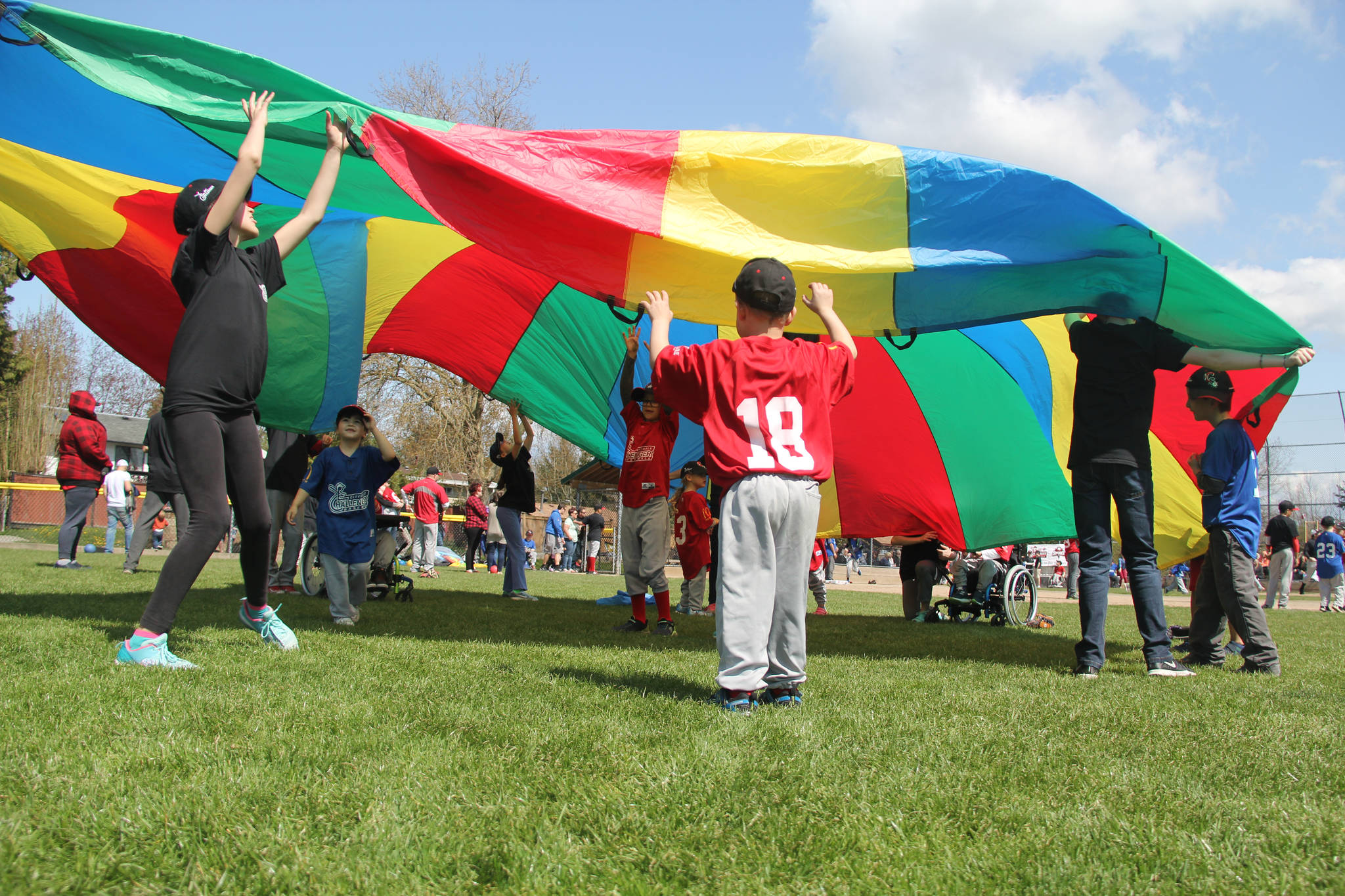 Some of the Challenger players were enjoying parachute games in the outfield while they waited for their turn up to bat. (Grace Kennedy photo)