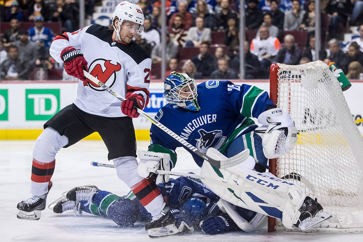 New Jersey Devils' Blake Coleman, left, watches the puck go wide of Vancouver Canucks goalie Jacob Markstrom, right, of Sweden, as Nikolay Goldobin, of Russia, slides into Markstrom during the first period of an NHL hockey game in Vancouver, on Friday March 15, 2019. THE CANADIAN PRESS/Darryl Dyck
