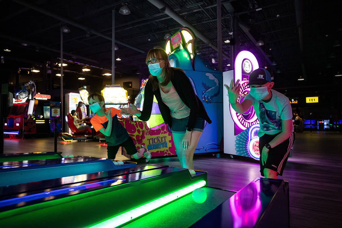 Reanna Balmer, centre, and her sons Barrett, left, 7, and Treydan, 11, wear protective face masks as they play Skee-Ball at Central City Fun Park on their opening weekend, in Surrey, on Sunday, June 7. (Photo: THE CANADIAN PRESS/Darryl Dyck)